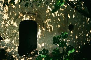 Door to Old Times: a doorway of an ancient house carved into the rock of the mountain; history of a fairy tale (italy)