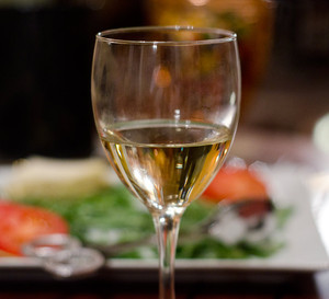 White wine: Glass with white wine (Cabernet Sauvignon), slightly chilled glass with salad in background