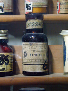 Ye Olde Naphtol Bottle: An old apothecary bottle or flask, on display on a shelf.