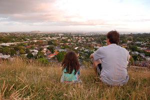 Father and daughter: Father and daughter looking out from a hill over a city