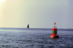 Waddenzee: Buoy and small sailing ship on the ocean.