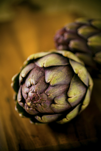 Two organic artichokes.: Two organic artichokes on a wooden board.
