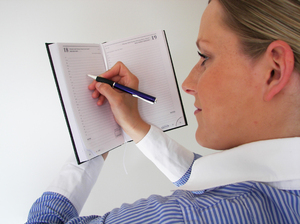 Woman writing in the agenda