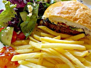 Burger and fries: Close up of burger and french fries (chips) with salad and sauce