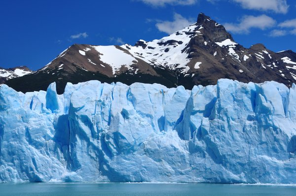 Glacier and mountains: Glacier wall and mountains in the background, against blue sky, in Patagonia, Argentina