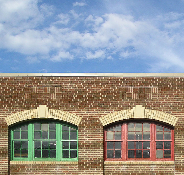 Windows in Brick: colorfully painted windows in brick building against blue sky