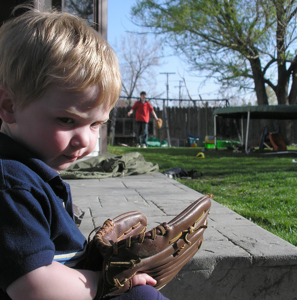 Baseball Kid: A toddler  holding a baseball glove watches other people play
