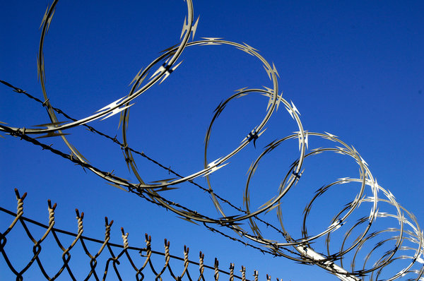 Razor Wire: Razor wire and barbed wire at the top of a chain link fence. Not a friendly place.