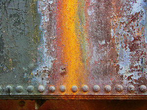 Old locomotive plate: Rusted metal sheet with a single-row riveted joint. Different textures in the series.