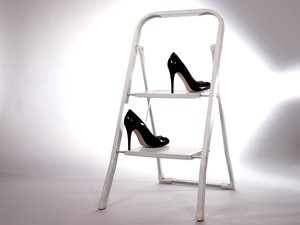 High heels on a step ladder: A pair of womens high heel shoes on a small step ladder