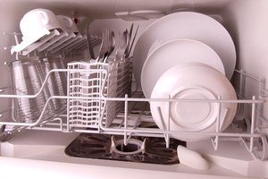 Dishwasher: A small dishwasher with clean crockery with open front.