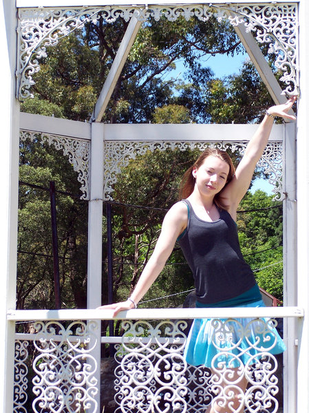 lacy frame for girl: wooden pergola frames girl in white lace.  Oops! she is squinting because of the bright light!