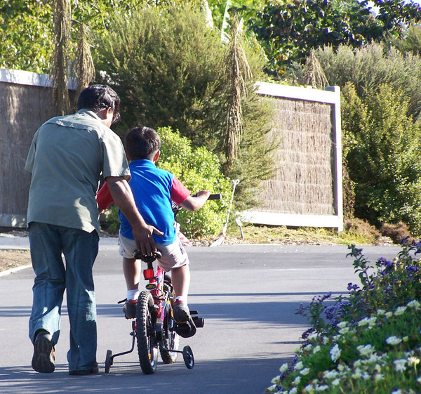 A helping hand 2: A parent gives their son a helping hand as they learn how to ride their bike.