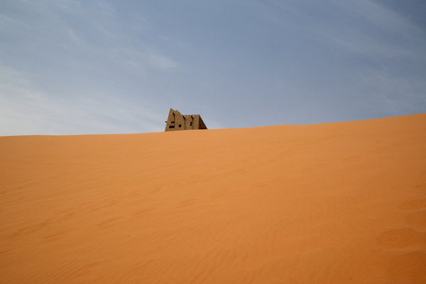 Dune building: A traditional-style building on the top of an enormous sand dune in the Tengger desert, China.