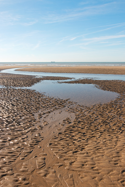 Beach at low tide: A soft sand beach at low tide at Camber Sands, East Sussex, England.