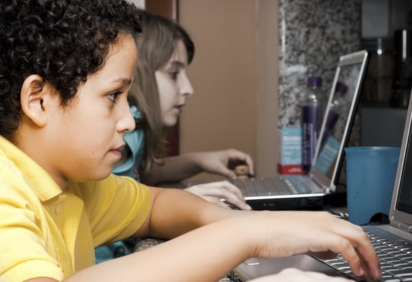 Online kids: A boy and a girl plugged on the web