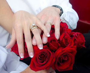 Roses 'n' rings: Hands laid on a red rose bouquet by newly weds.