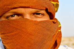Arab man with head scarf: Portrait of Arab man in the desert of Saudi Arabia, he is wearing head scarf, or keffiyeh as it is called Skin dark and red from the heat and sand all around him .  Photo image for wall art, artwork or local art . Burka is covering his head except his eye