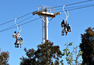 above the trees: cable chairlift in operation - people passing each other