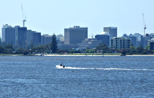 river crossing: couple motoring across the river to the city centre - CBD,