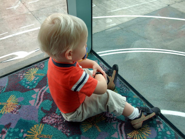 airport watch & wait2: toddler waiting in international airport departure lounge and watching tarmac activities