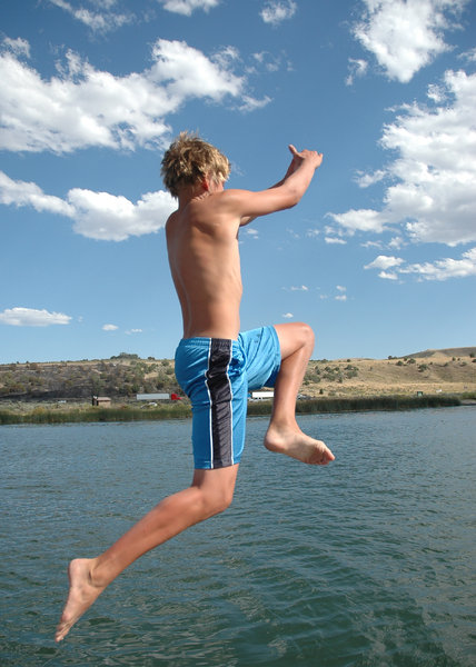The Leap: Boy jumping from a boat into a lake.