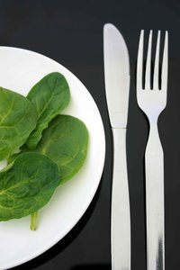 Spinach Diet: Spinach leaves on a white plate with knife and fork