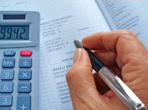 Business Accounts: Hand with a pen over an accounts book