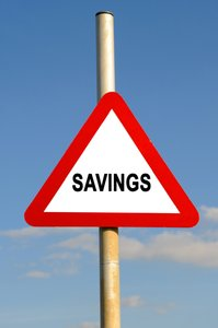 Savings Triangle Warning Sign: Red triangle savings warning sign against a blue sky background