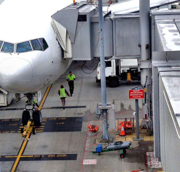 aircraft serviced in the rain3: airport tarmac vehicles and trolleys – unloading and loading international flight