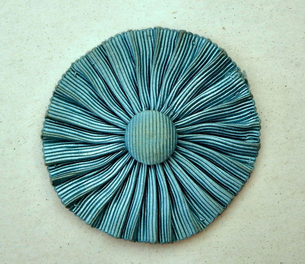 faded riibbed rosette1.: faded cloth flower-like ribbed rosette
