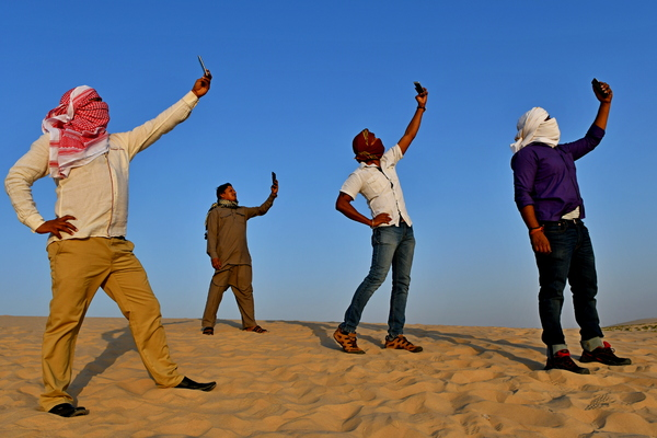 Male models making selfies: Male models from India are posing on the sand making Selfies with their phones. Men from India are running and playing in the desert sand in Saudi Arabia. Sunlight is strong and sky is blue and the desert men are having fun like desert people in the hot d