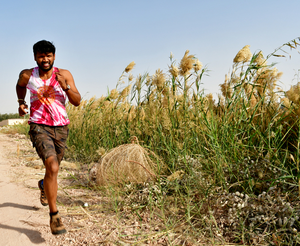 Running man: Young man Jogging in nature for fitness and healthy weight loss. Nature greenery is around and the young adult is running wearing sport clothes and shorts.  Healthy lifestyle and body care are important for men and women