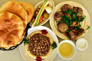 Arabic breakfast with falafel: Falafel and Hummous ! Hummous with meat and beans and salad on the side . Arabic traditional breakfast or snack during the day. This food is popular among all crowds and people of all ages they love to eat it in Saudi Arabia, Jordan, Lebanon, Syria, Iran,