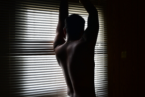 Standing in the dark: Fitness model standing and facing out the window through the striped patterned light and shadow shuttering. The  man is in darkness and his body in dark shadows almost silhouette.