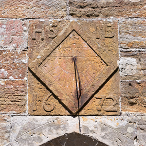 Old sundial: A sundial on the wall of an old parish church in Sussex, England.
