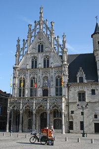 Barrel organist: A musician playing a barrel organ in front of the town hall in Mechelen, Belgium.
