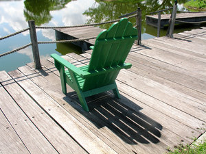 Chair By The Lake: Green lounge chair overlooking a lake by the boardwalk.