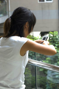 Communication: Asian woman entering a text message on a mobile phone.