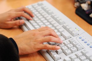 Woman using computer: Hands of woman using a computer at the office