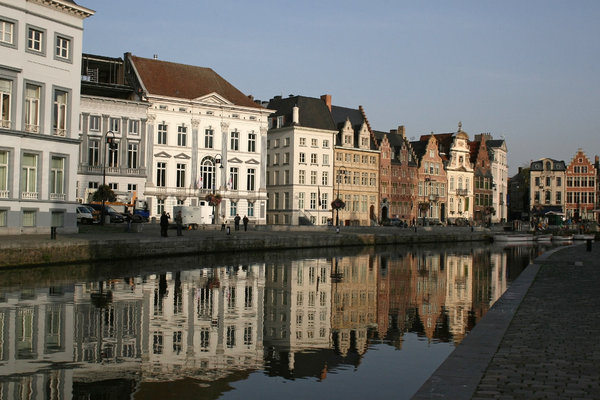 Morning reflections: Reflections in the canal of the historic merchant houses of the Graslei, Ghent, Belgium, in early morning.