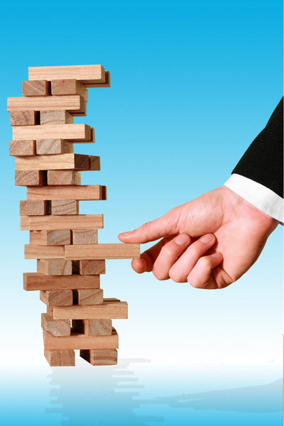 Business Decision: Tower of wooden blocks being removed by a hand