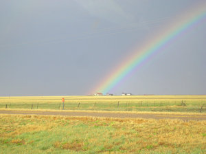 Under the rainbow: A real rainbow ending at a farm house