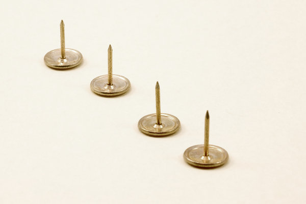 Four pins 2: Close-up of drawing pins or upholstering pins
