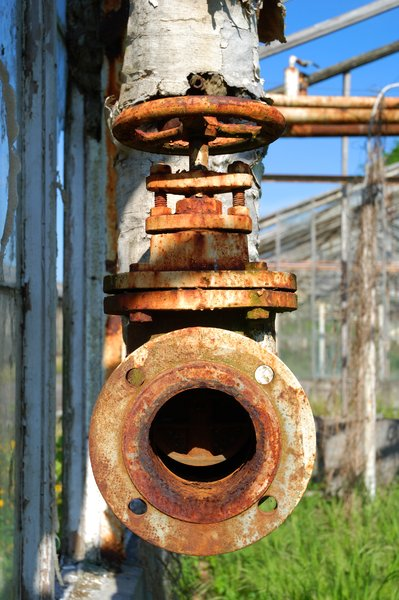 Pipe and Tap: PLEASE RATE THIS PHOTO!Old and decayed pipe and tap in an abandoned greenhouse facility.