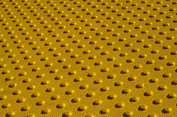Crosswalk warning bumps: Tactile warning bumps at a city crosswalk.