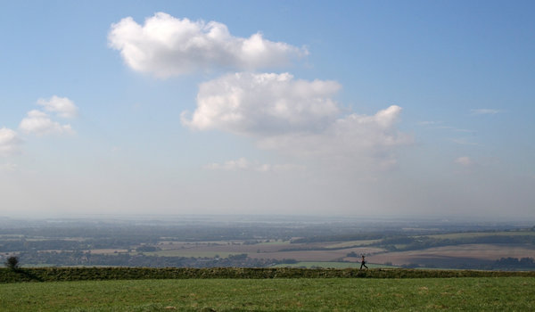 Jogger: A jogger running along a ridge on the South Downs, West Sussex, England, in spring.