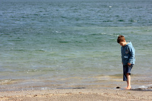 Boy by the lake: Springtime at the lake, too cold to swim but not too cold to test the water