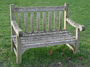 Traditional garden bench: A traditional wooden bench in a garden in Kent, England.