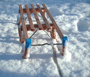 Sledge 1: A wooden sledge or toboggan in the snow